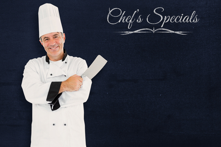 holding a knife: Composite image of friendly chef holding a knife against a blackboard Stock Photo