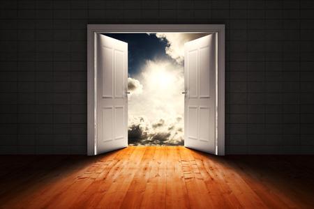 door opening: Door opening in dark room to show sky against dark sky with white clouds Stock Photo