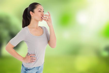 asthmatic: Asthmatic pretty brunette using inhaleragainst glowing sky above field