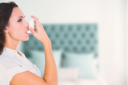 asthmatic: Asthmatic brunette using her inhaleragainst pillow in a bed