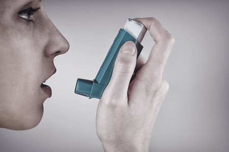 asthmatic: Close up on an asthmatic womanagainst grey vignette Stock Photo