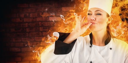 satisfying: Portrait of a woman chef satisfying against image of a wall