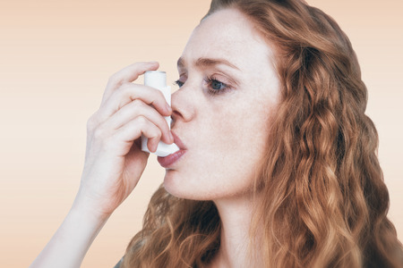 health fair: Close-up of woman using the asthma inhaler against orange background Stock Photo