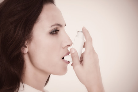 asthmatic: Asthmatic brunette using her inhaleragainst white background with vignette