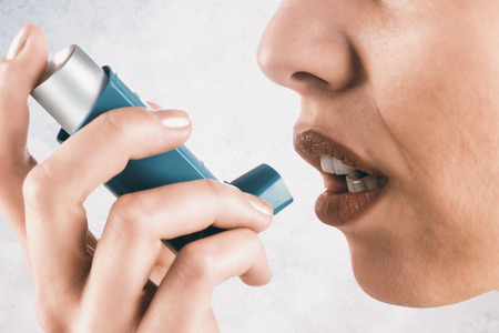 asthmatic: Close up on an asthmatic womanagainst grey background