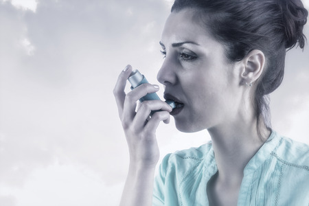 asthmatic: Portrait of an asthmatic womanagainst beige background Stock Photo