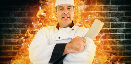 holding a knife: Portrait of a serious chef holding a knife against image of a wall