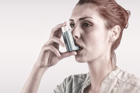 asthmatic: Portrait of a asthmatic womanagainst blue background Stock Photo