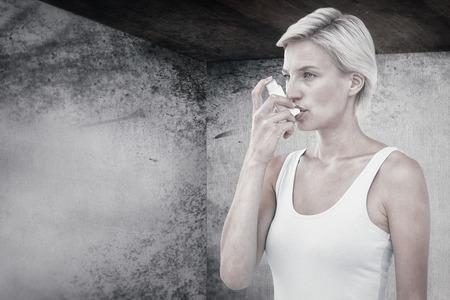 inhaler: Blonde woman taking her inhaler against image of room corner Stock Photo