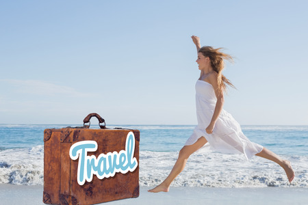 maxi dress: Beautiful blonde in white sundress jumping up on the beach against suitcase with the message travel