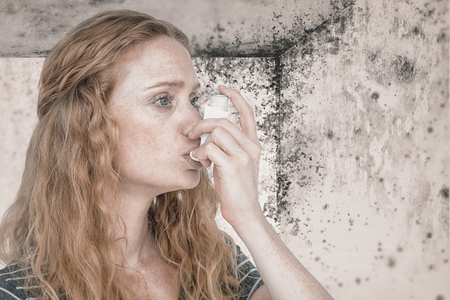 health fair: Woman using the asthma inhaler against image of a room corner Stock Photo