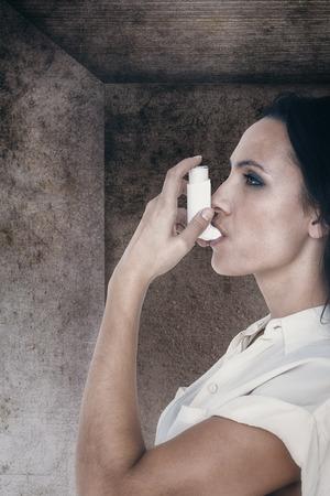 asthmatic: Asthmatic brunette using her inhaleragainst image of room corner Stock Photo