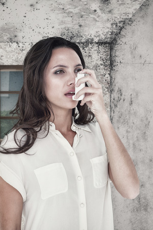 asthmatic: Asthmatic brunette using her inhaleragainst image of a room corner