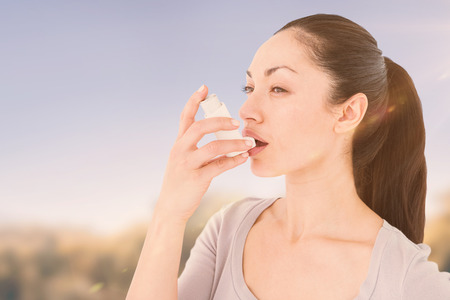asthmatic: Asthmatic pretty brunette using inhaleragainst park on sunny day Stock Photo