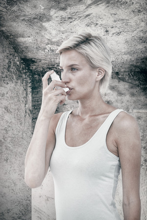 dirty blond: Blonde woman taking her inhaler against image of room corner Stock Photo