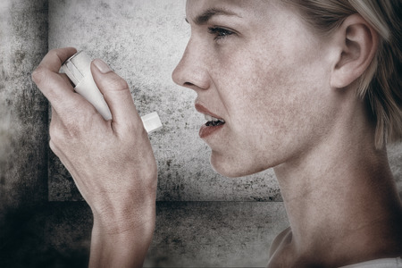 health fair: Asthmatic pretty blonde woman using inhaler against image of room corner Stock Photo