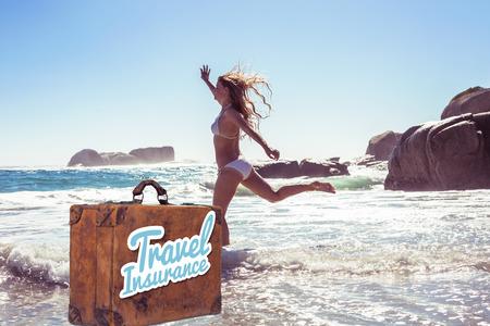 Mooie glimlachende vrouw in witte bikini overslaan op het strand tegen reisverzekering bericht op een oude koffer