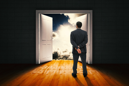 door opening: Rear view of classy businessman posing against door opening in dark room to show sky