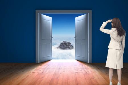 door opening: Rear view of young businesswoman looking away against door opening in dark room to show sky