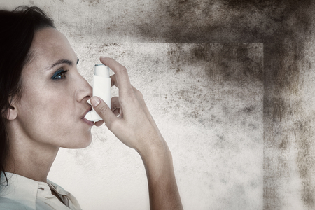 inhaler: Asthmatic brunette using her inhaler  against image of room corner