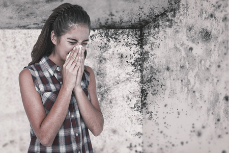 affliction: Sick blonde woman sneezing in a tissue against image of a room corner