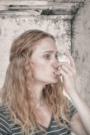 inhaler: Woman using the asthma inhaler against image of a room corner Stock Photo