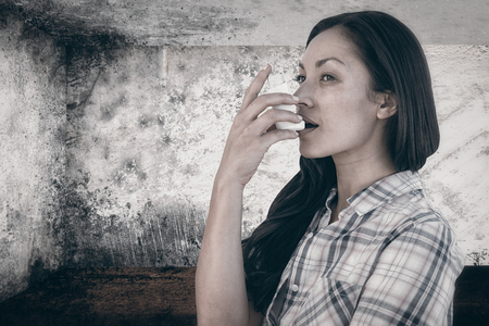 affliction: Portrait of an asthmatic woman  against image of room corner Stock Photo
