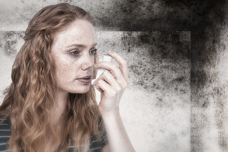 affliction: Beautiful woman using the asthma inhaler against image of room corner