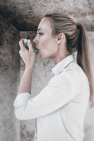 inhaler: Beautiful blonde using an asthma inhaler against image of room corner Stock Photo
