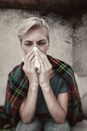 blowing nose: Sick blonde woman blowing her nose  against image of room corner Stock Photo