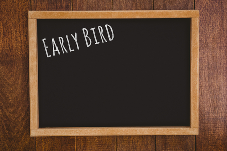 early: Early bird message  against a black board is posing on a wall Stock Photo