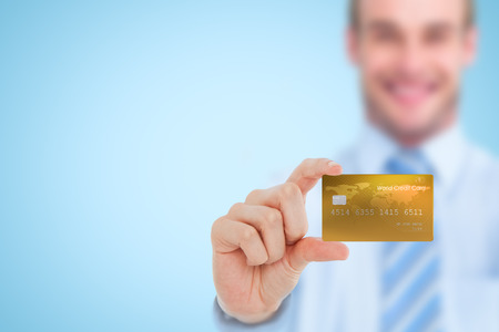 creditcard: Happy businessman showing a creditcard against blue background