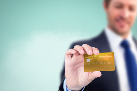 creditcard: Businessman showing a creditcard against blue background