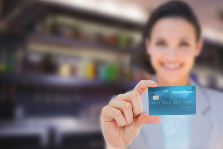 creditcard: Composite image of happy businesswoman showing a creditcard Stock Photo