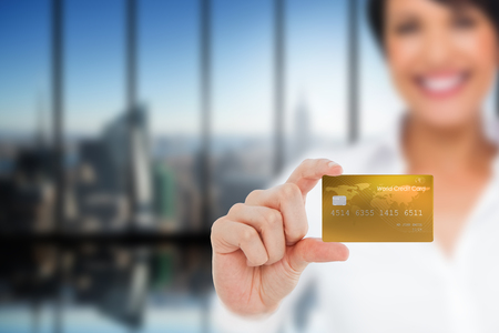 creditcard: Happy businesswoman showing a creditcard against room with large window looking on city Stock Photo