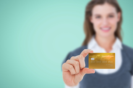 creditcard: Happy businesswoman showing a creditcard against green background