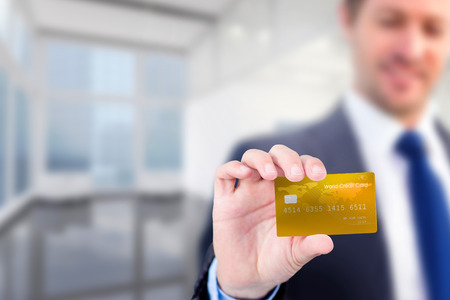 creditcard: Businessman showing a creditcard against modern room overlooking city Stock Photo