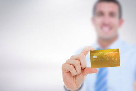 creditcard: Happy businessman showing a creditcard against grey background