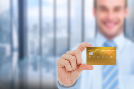 creditcard: Happy businessman showing a creditcard against room with large window looking on city