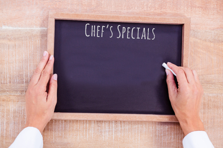 hight tech: Composite image of chef hand writing on a chalkboard on a wooden desk Stock Photo
