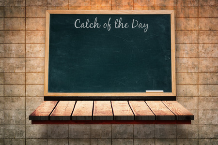 wooden shelf: Catch of the day message against black board on a wooden shelf