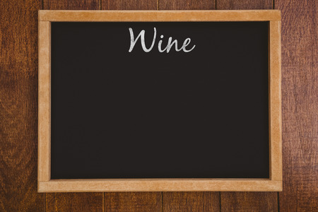 reaping: Wine message against a black board is posing on a wall Stock Photo