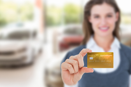 creditcard: Happy businesswoman showing a creditcard against view of row new car Stock Photo