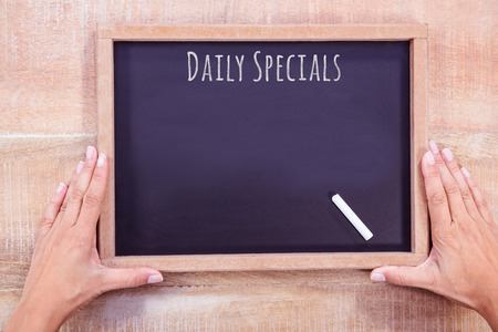 specials: Daily specials message against hand writing on chalkboard Stock Photo