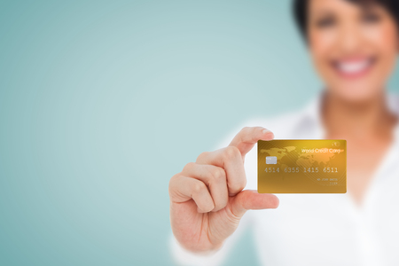 creditcard: Happy businesswoman showing a creditcard against blue background