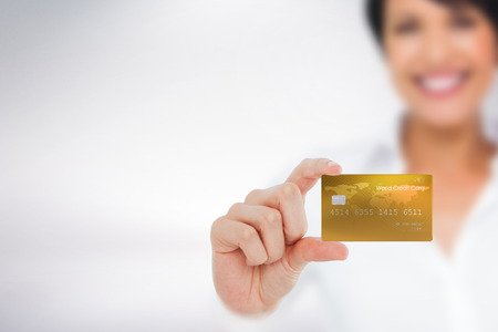 creditcard: Happy businesswoman showing a creditcard against grey background