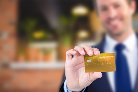 creditcard: Happy businessman showing a creditcard against empty counter at coffee shop Stock Photo