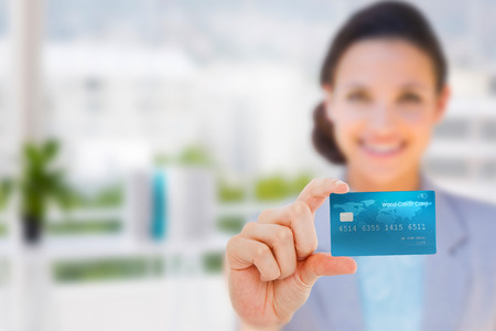 creditcard: Happy businesswoman showing a creditcard against office