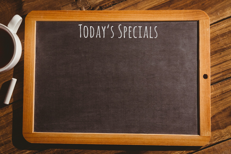 composite image: Composite image of a chalkboard with coffee mug on a wooden desk Stock Photo