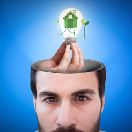 mid adult men: Hand holding environmental light bulb against blue background digitally generated blue design background